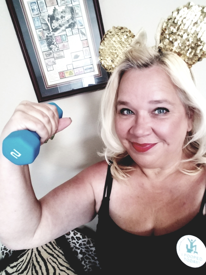 the disabled diva wearing gold Minnie mouse ears and holding handweights